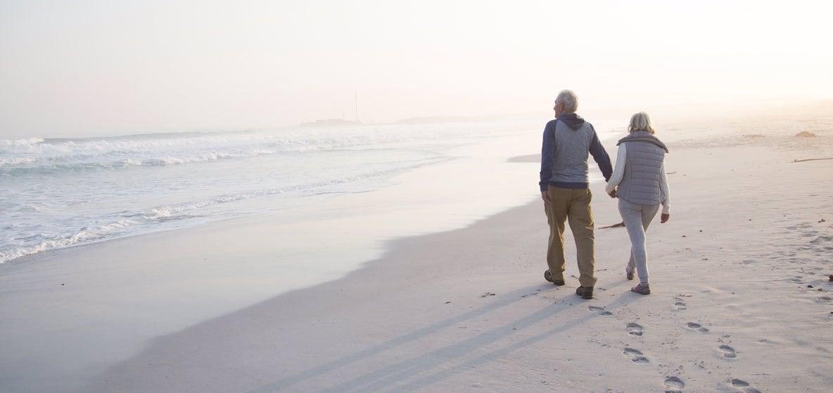 Seniorenpaar loopt op het strand