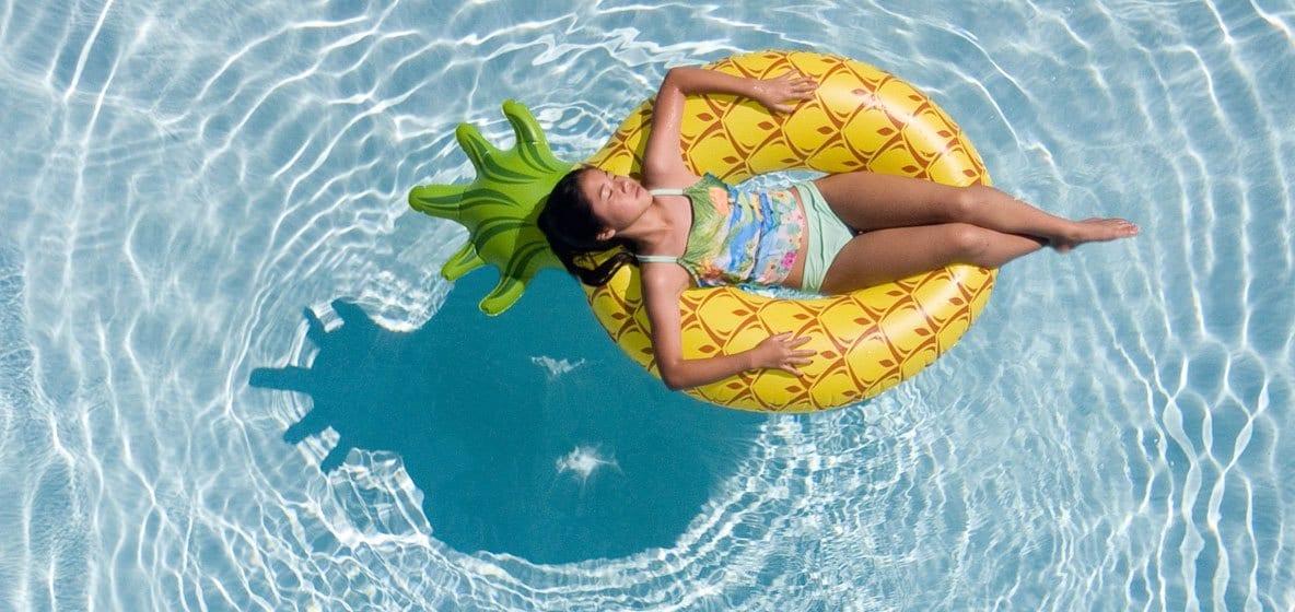 Meisje ligt in een zwemband in het water