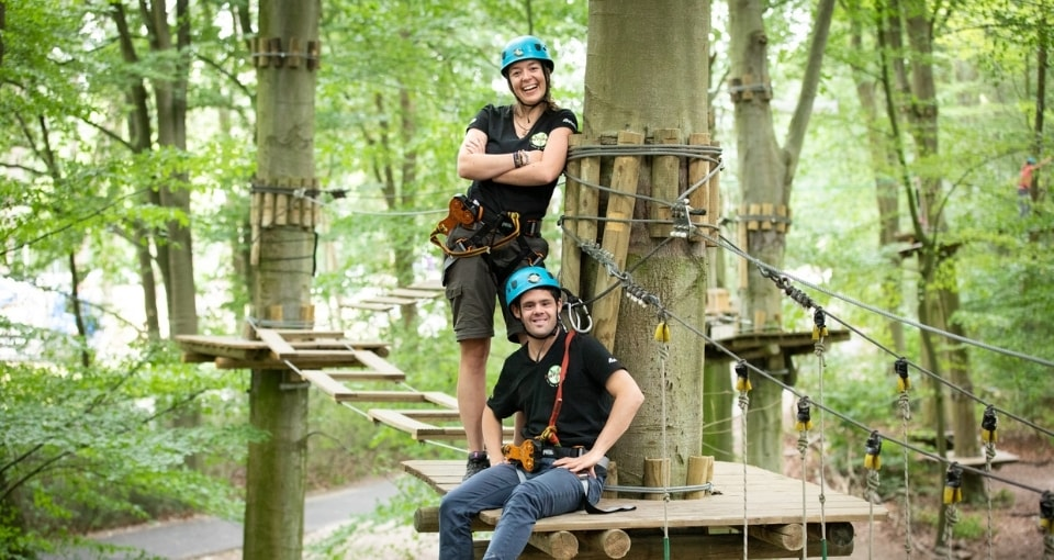 Two people standing in a tree at Fun Forest