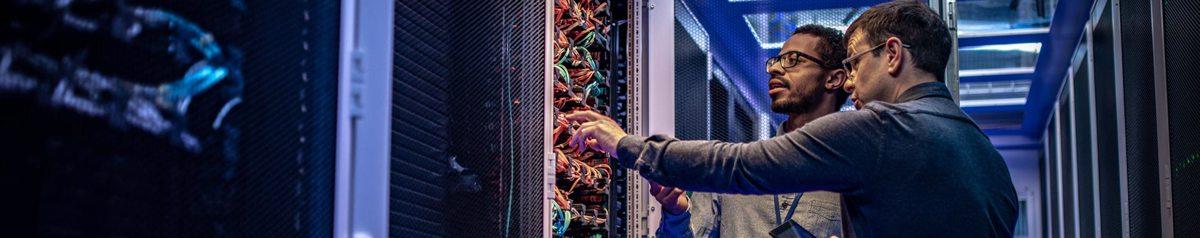 Twee mannelijke ingenieurs bij serverkast met diverse kleuren kabels