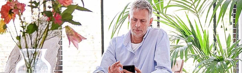 Man aan tafel met telefoon
