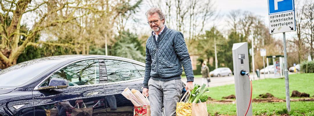 Persoon met boodschappentassen naast auto in laadpaal