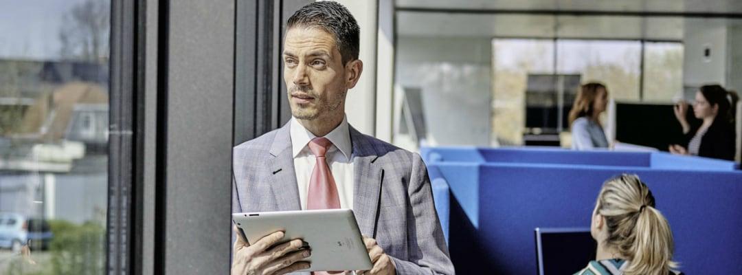 Man op tablet kijkt naar buiten