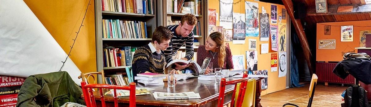 Drie studenten rond tafel in bibliotheek