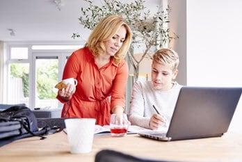 Moeder helpt zoon met huiswerk