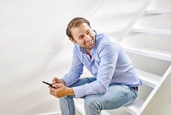 Man checkt mobiel zittend op de trap in huis