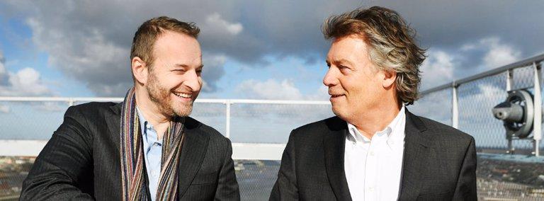 Twee vastgoedbeleggers staan op dak gebouw en schudden elkaar de hand