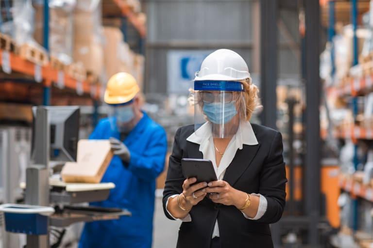 Twee werknemers met mondkapje in werkplaats