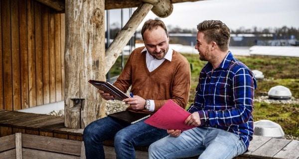 Twee ondernemers buiten met documenten