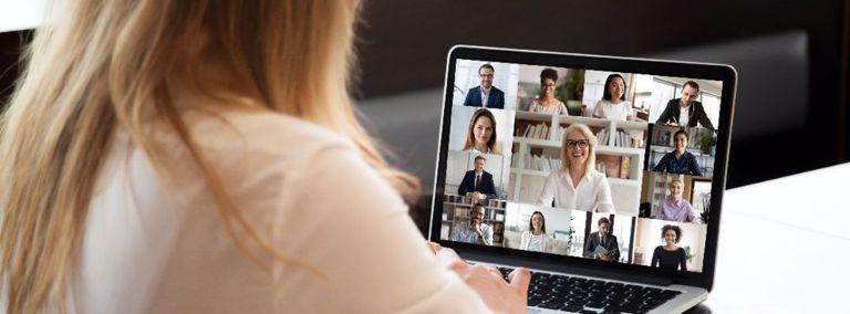 Vrouw kijkt naar laptop met concerence call scherm