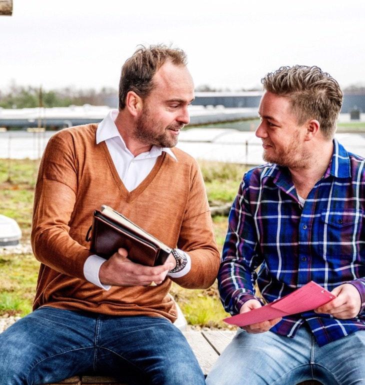 Twee mannen met documenten bij een weiland