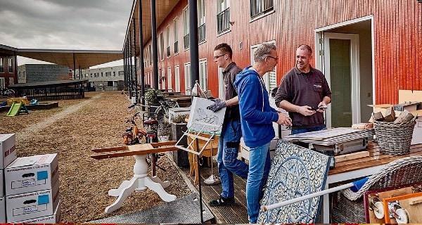 Drie witte mannen buiten een woning aan het verhuizen