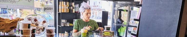 Klant in groene jurk rekent af met pin in banketbakkerij
